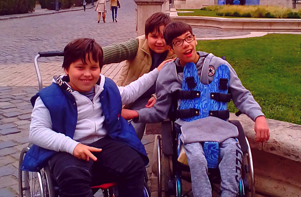The students of the School of Tomorrow (three preteen boys, two of them in wheelchairs) hugging and smiling on a school trip.